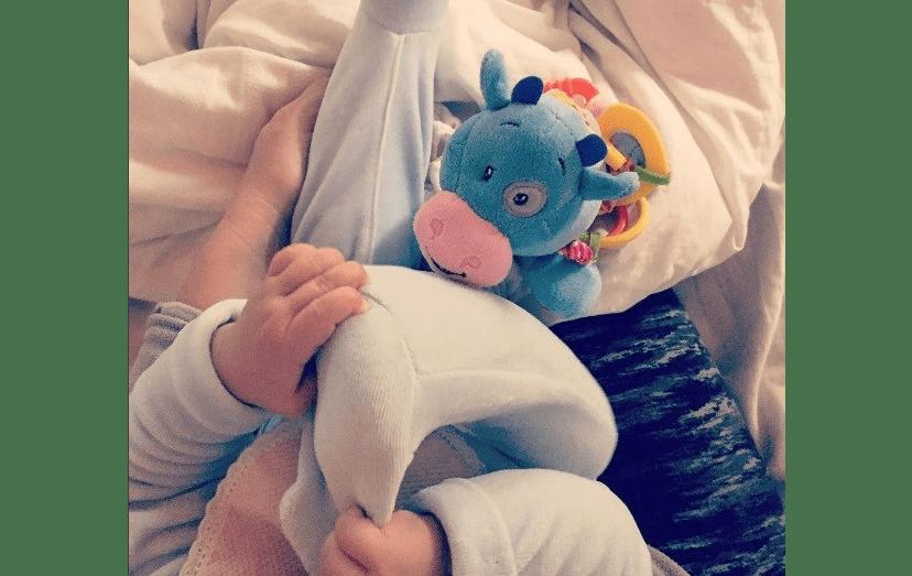 Uma imagem ternurenta da bebé, deitada no berço
