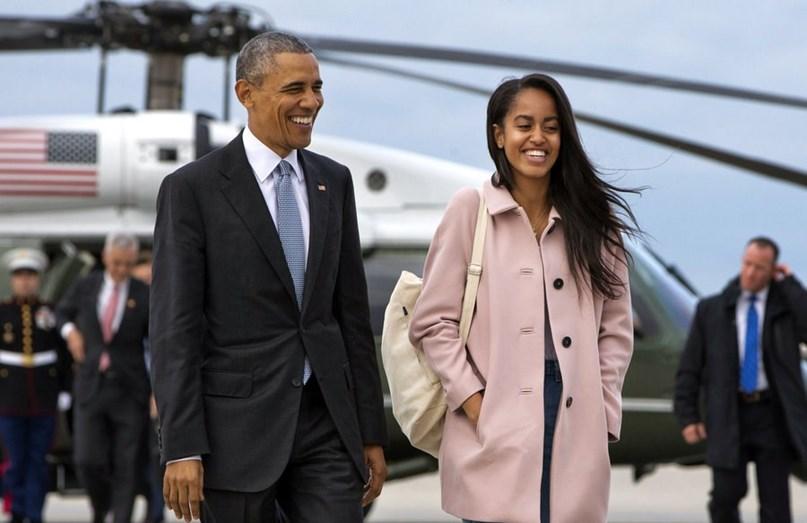 Barack e Malia sorridentes à saída de uma avião