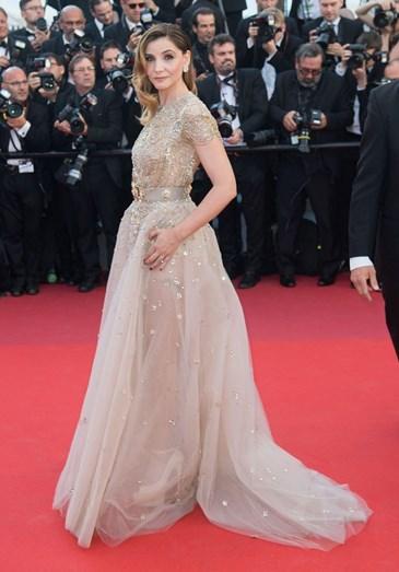 Clotilde Courau com um vestido nude de transparências e brilho