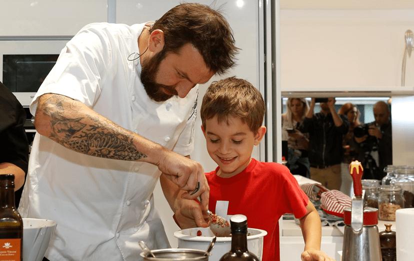 Um dos momentos carinhosos de Ljubomir com um pequeno aluno de Cozinha.