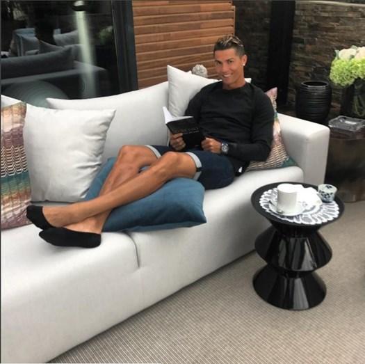 Cristiano Ronaldo a ler o livro de auto-ajuda, enquanto bebe chá